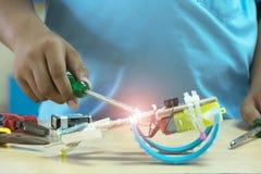 有创造机器人的螺丝刀的手 免版税库存照片