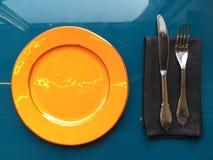有利器的橙色光滑的板材在一块黑暗的餐巾 免版税库存图片