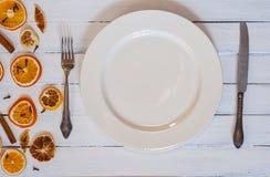 有利器的白色空的用餐的板材白色木表面上 库存图片