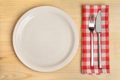 有利器的空的板材在木背景的红色方格的餐巾 免版税库存照片