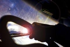 有刮水器的肮脏的被抓的汽车挡风玻璃通过被弄脏的方向盘用在被弄脏的背景的司机的手 库存照片