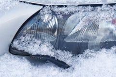 有刮水器的车灯在雪下 免版税图库摄影