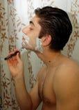 有刮的泡沫人在他的在刮镜子前的面孔 免版税图库摄影