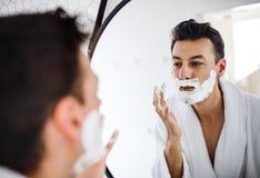有刮的泡沫在卫生间里早晨,每日惯例年轻人 库存图片