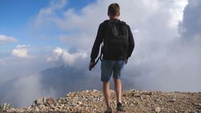 有到达山上面与多云天空的在背景和举手的背包的年轻男性徒步旅行者 男孩游人 股票录像