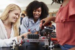 有制造机器人车的母学生的老师在科学教训 免版税库存照片