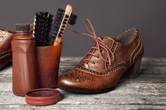 有刷子和擦亮剂奶油的布朗鞋子 免版税库存照片
