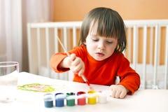 2年有刷子和树胶水彩画颜料油漆的男孩在家 免版税库存照片