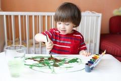 有刷子和树胶水彩画颜料的小男孩 免版税图库摄影