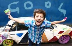 有刷子和街道画的少年英俊的男孩 库存图片