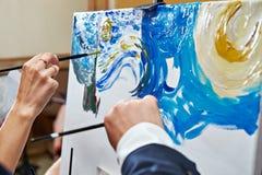 有刷子油漆图片的手 免版税库存照片