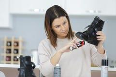 有刷子清理黑色皮鞋的女性 免版税库存照片