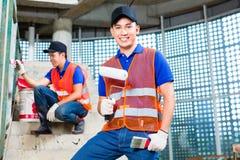 有刷子的亚裔在建造场所的画家和油漆 免版税库存图片