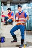 有刷子的亚裔在建造场所的画家和油漆 库存图片