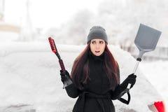 有刷子的取消雪的女孩和铁锹从汽车 免版税库存照片