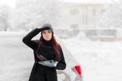 有刷子的取消雪的女孩和铁锹从汽车 图库摄影