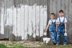 有刷子的在老墙壁的男孩和油漆 免版税库存图片
