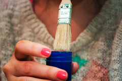 有刷子的妇女和罐蓝色油漆 库存图片