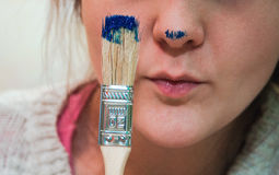 有刷子的妇女和罐蓝色油漆 免版税库存照片