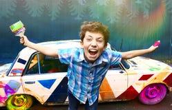 有刷子的少年英俊的男孩和街道画喷洒 免版税库存图片