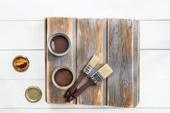有刷子的木箱和开放罐头油漆和污点 图库摄影