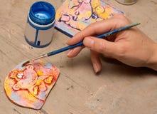 有刷子的艺术家手在处理绘画黏土盘区 免版税图库摄影