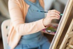 有刷子绘画的艺术家在艺术演播室 图库摄影