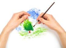 有刷子绘画自然风景的人的手 免版税库存图片
