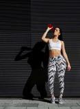 有刷新与能量饮料的美好的图的年轻人适合的妇女对黑墙壁在城市 免版税图库摄影