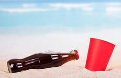 有刷新的饮料的在沙子的瓶和玻璃 免版税库存图片