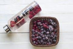 有刷新的饮料的,与草莓切片的水瓶,与hashtag生活和篮子用冷冻莓果在木背景 库存图片