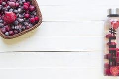 有刷新的饮料的,与草莓切片的水瓶,与hashtag生活和篮子用冷冻莓果在白色背景 免版税库存照片