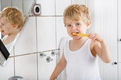 有刷他的牙的蓝眼睛和金发的逗人喜爱的小孩 免版税库存照片