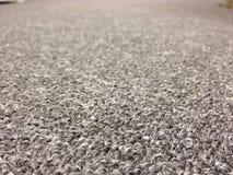 有前景的灰色办公室地毯在焦点 免版税库存图片