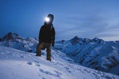有前灯和背包佩带的滑雪的人佩带在惊人的冬天山景前面的身分 旅客攀登在的晚上 免版税图库摄影