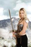 有剑和山的女性战士在背景中 免版税库存图片