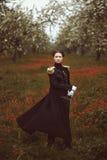 有剑的不可思议的俏丽的女孩在花的领域站立 风翻动外套 免版税库存图片