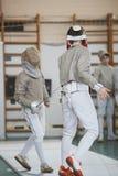 有剑的两个少年击剑者在剑术竞争 库存图片