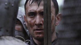 有剑的中世纪骑士在他的面孔附近在雨中,关闭 股票录像