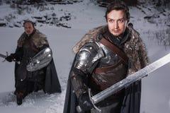 有剑的中世纪骑士在装甲当王位样式比赛  免版税库存照片