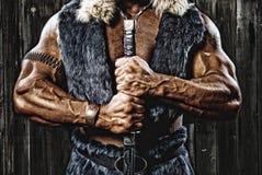 有剑的坚强的肌肉人防御者战士在手中 库存照片