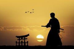 有剑的日本人在日落 库存图片