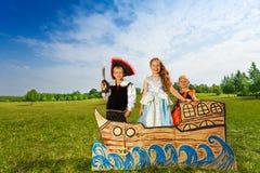 有剑的海盗和两位公主在船站立 免版税库存图片
