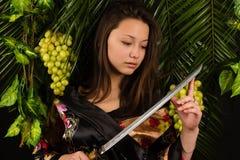 有剑的美丽的亚裔女孩 图库摄影