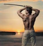 有剑的肌肉英俊的人在日落 免版税库存图片