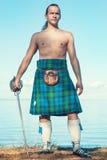 有剑的苏格兰人在海附近 库存照片