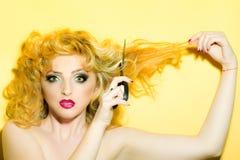 有剪刀的性感的金发碧眼的女人 库存图片