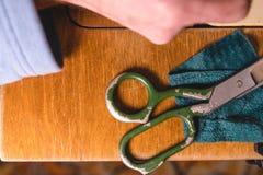 有剪刀的老缝纫机,在一个老脏的工作表上 裁缝` s工作表 纺织品或美好布料做 工业fabri 图库摄影
