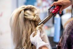 有剪刀头发圈子的美发师手称呼了金发碧眼的女人 免版税库存图片