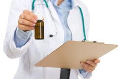 有剪贴板和医学瓶的医生妇女 免版税库存图片